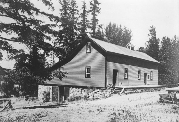 Black and white photo of a one and a half storey building set into a hill. The lower back of the building has a stone foundation and barn doors.