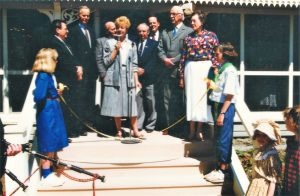 Colour photo, a group of people standing on the verandah. A woman in the middle is speaking into a microphone.