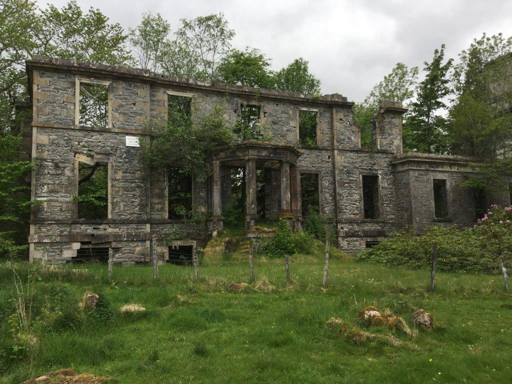 Colour photo of the remaining front wall of the ruins of a stone building.