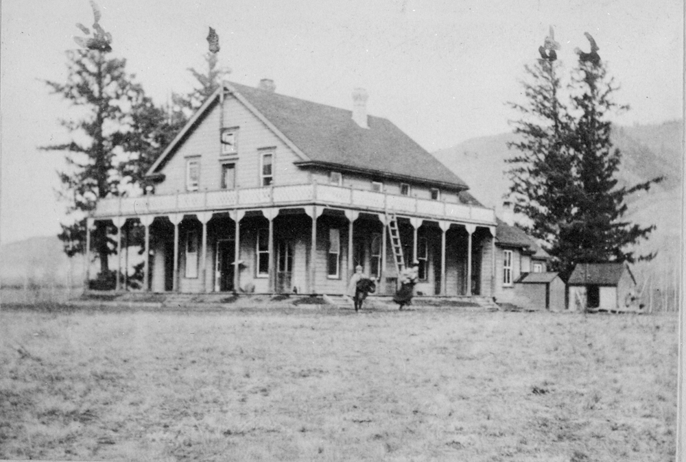 Black and white photo of the front and side of a two-storey house with a wrap-around verandah and balcony. There are two children standing in front of the house.
