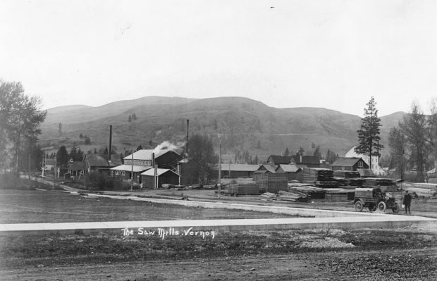 Black and white photo of three small wooden industrial buildings next to a road, with hills behind.