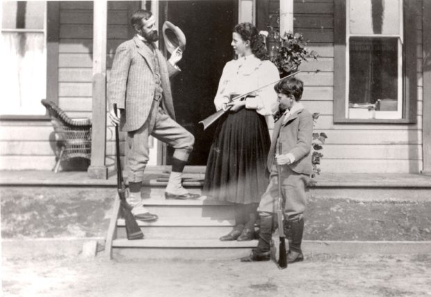 Black and white photo of a man, a girl, and a younger boy standing on the house steps casually holding rifles.