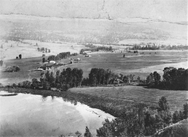 Black and white photo of distant farm buildings and some trees with a lake in the lower-left corner.