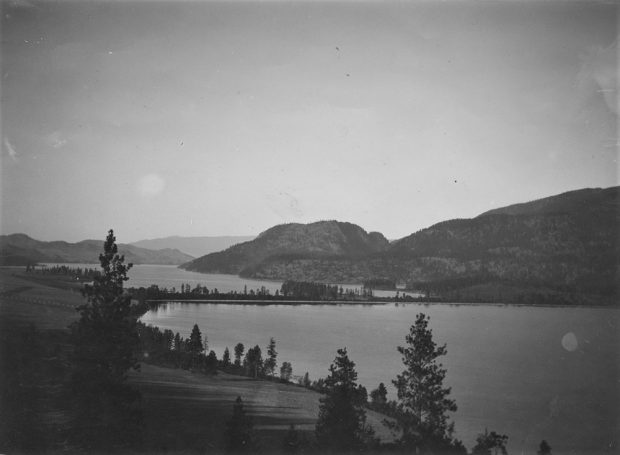 Black and white photo of view of two lakes with a narrow isthmus with low hills in the distance.