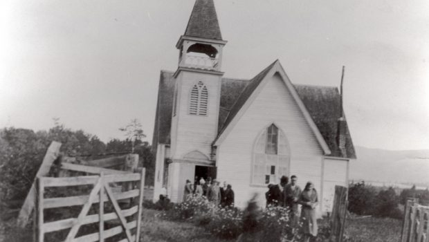 Black and white photo of a group of men and women leaving a small church.