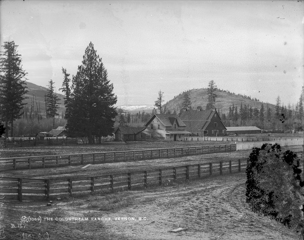 Black and white photo of farm fencing in front of barns and trees with distant hills.
