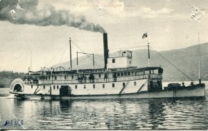 Black and white postcard of a large paddlewheeler with two decks and smoke billowing from the stack.