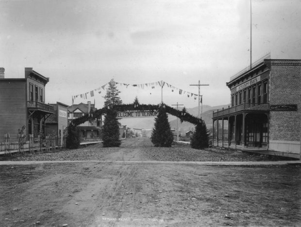 Black and white photo of a gravel road with commercial buildings on each side. Crossing the road is an evergreen Welcome sign.