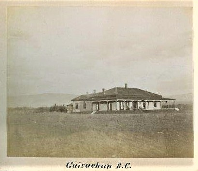 Black and white photo of the front and side of a one-storey house with a wrap-around verandah with a field in front.