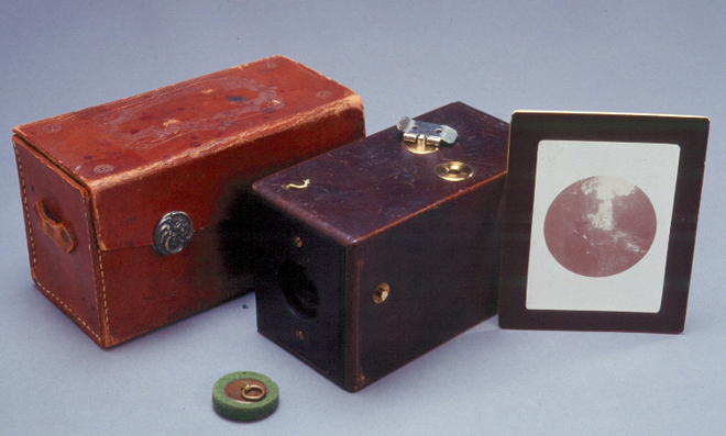 First Kodak box camera, with a case, and a framed photo