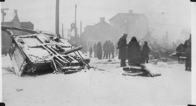 Photograph of the wrecked third coach of the Ottawa Valley Local in Almonte with people walking through town, 1942