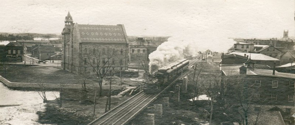Photograph of a train travelling on a track with Almonte town hall in the background, 1950s