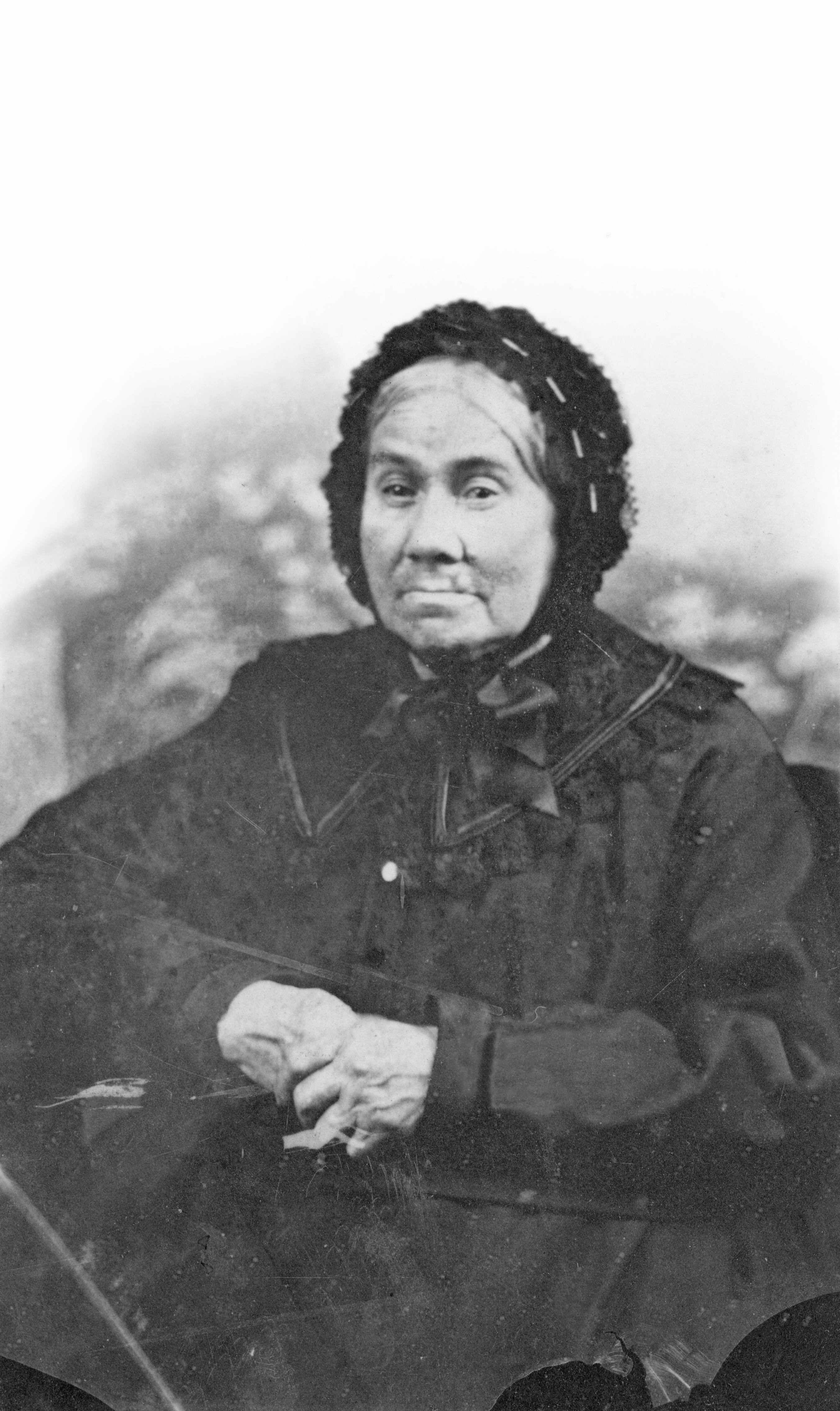 Sepia-tone photograph of an elderly woman, clad in a long black dress with a wide lace collar. Her white hair is tied in a bun behind her head and covered in a black lace bonnet (a béguin) tied with a large ribbon under her chin. Her hands, crossed on her lap, reveal fingers twisted and worn by old age.