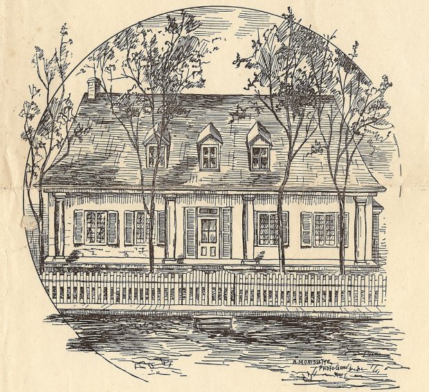 Engraving published in a newspaper, showing the façade of a rectangular one-and-a-half storey house with a steeply pitched roof having three dormers. A porch extends the full width of the house, with the roof overhanging it. A wooden fence runs along the dirt road in the foreground.