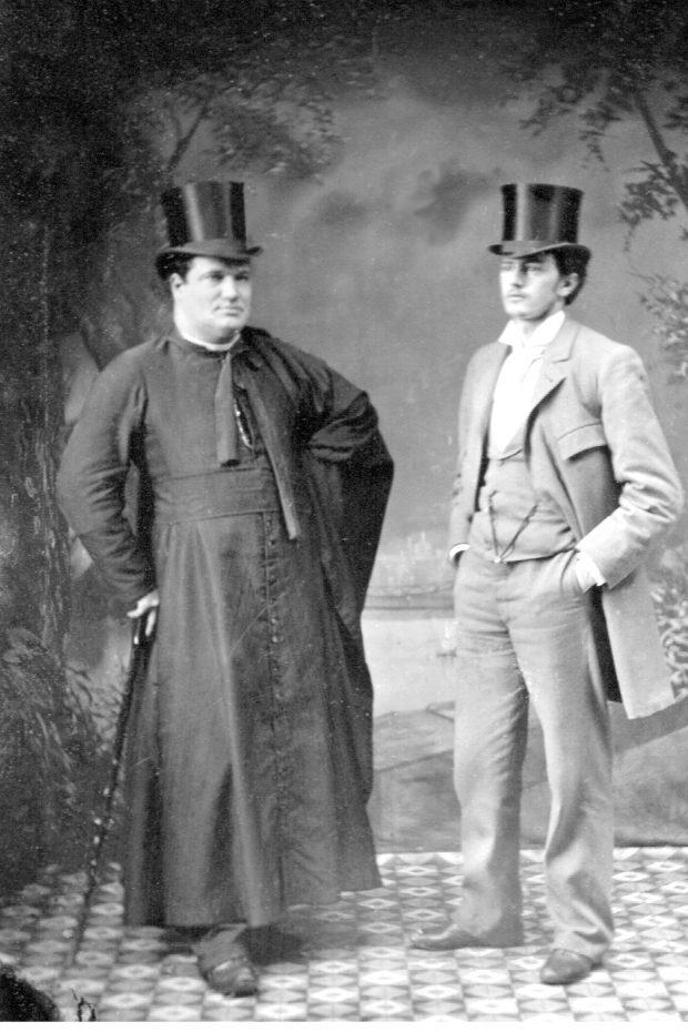 Black & white photograph of two men standing in photographer's studio. One of them, a priest, wears a black cassock and is leaning on a pommel cane. The other wears a light-coloured three-piece suit and stands with his hands in his pockets. Both wear top hats.