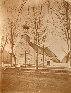 Sepia-tone photograph of the first Church in Saint-Jérôme. The church is built of fieldstone, as is the charnel house, visible to the right. Also seen at right are a number of small farm structures. A wooden sidewalk borders the dirt road in the foreground.