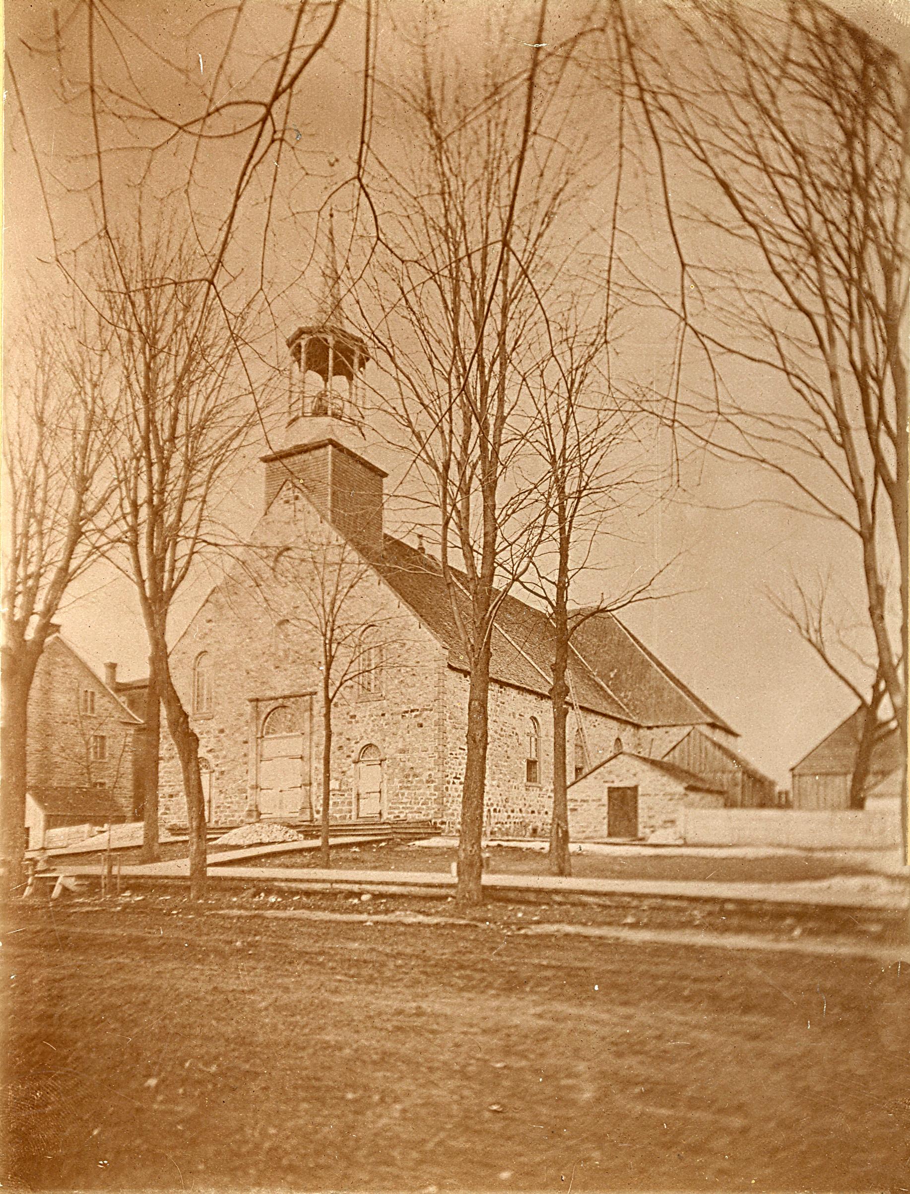 Photographie sépia de la première église de Saint-Jérôme. L'extérieur de l'église est en pierre des champs ainsi que le charnier situé à droite de l'église. Quelques petits bâtiments de ferme en bois se trouvent à droite de l'église. Un trottoir en bois longe une rue en terre devant le bâtiment.