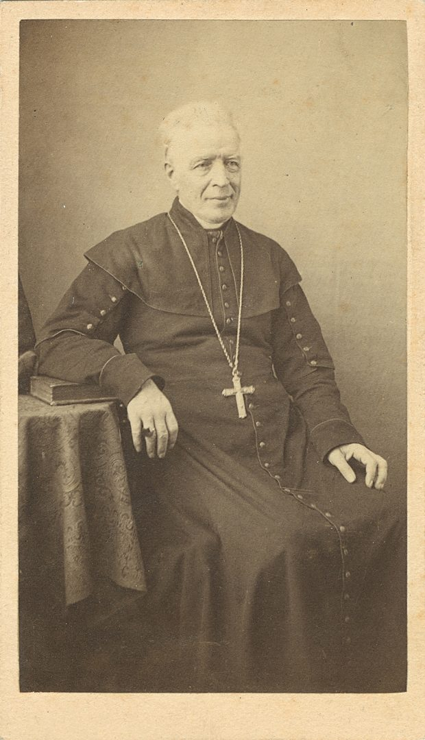 Sepia-tone photograph of a clergyman seated in a chair. He is elderly, with white hair. He wears a cassock, and a cross hangs from a long chain around his neck. His right hand rests on a table, with a ring visible on one finger.