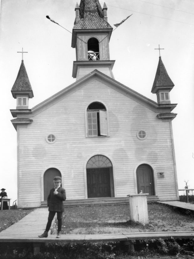 Black & white photograph of the façade of a small church. The clapboard building has three doors, three windows above the doors and a belfry. A boy stands on a boardwalk outside the church.