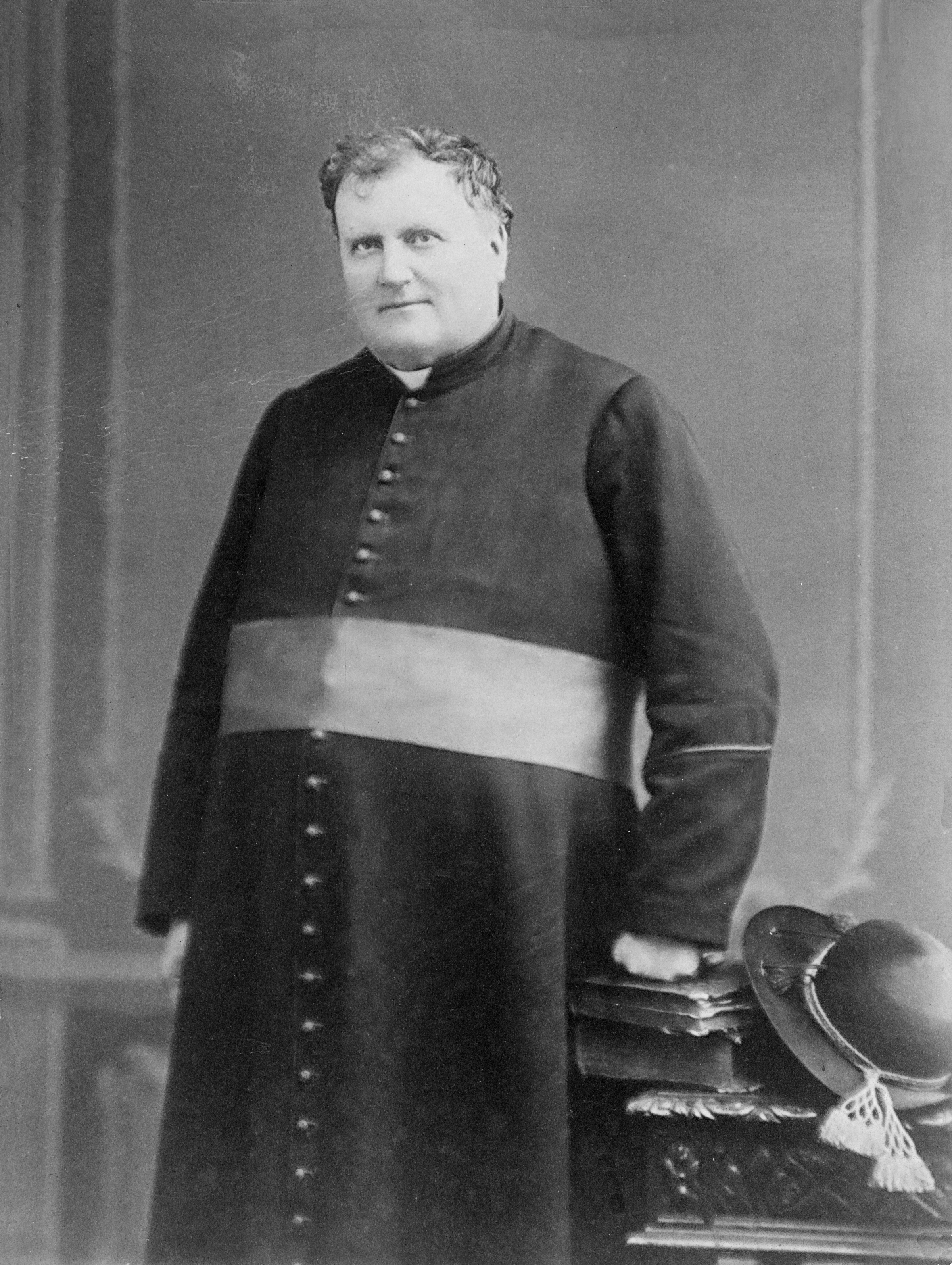 Black & white photograph of a man in his late fifties. He is standing and wears a cassock with a sash, symbolizing his status as Monseigneur. Two books and a felt hat rest on a low, carved table next to him. He rests his fist on the books.