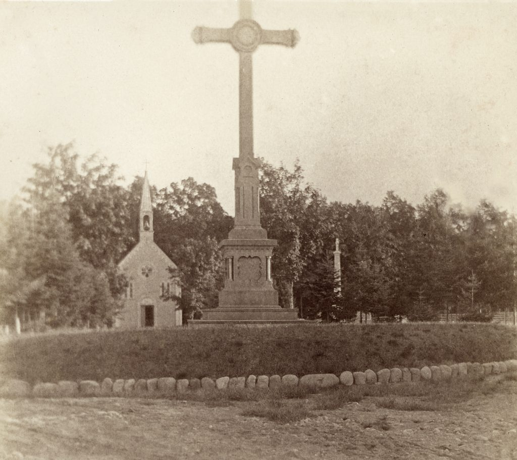 Black & white photograph depicting a cemetery in summertime. In the foreground is a sandy path, and behind it, a plant bed topped by a tall sculpted cross. Farther back, a small wooden chapel with a steeple is visible, surrounded by a few gravestones. In the background is a woodland.