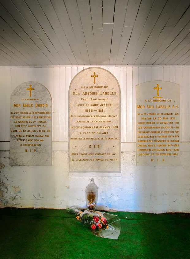 Colour photograph of a tomb in the basement of a chapel. Three white marble plaques with gold inscriptions are affixed to the wall. Beneath the central plaque, a bouquet of flowers and a glass urn site on the floor, which is carpeted in artificial grass.