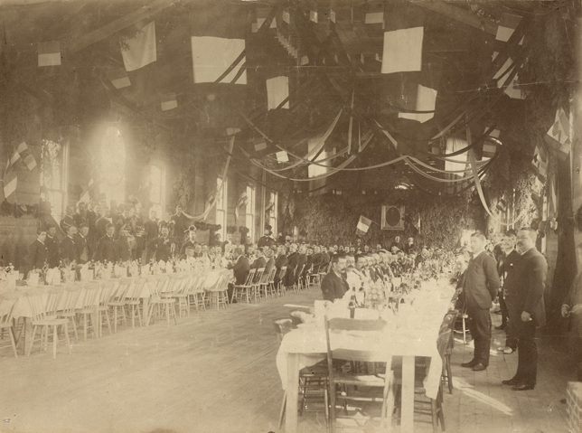 Sepia-tone photograph of a long, high-ceilinged reception hall, festooned with streamers, French flags and fir branches. Two long parallel tables are set for a meal, with several men seated at them. Members of a brass band stand against the wall to the left.