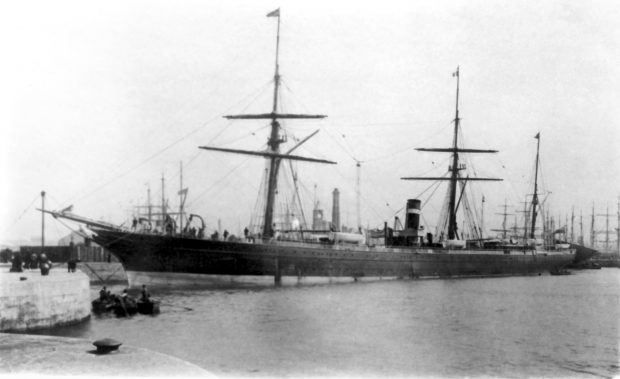 Black & white photograph of a sail and steam ship moored at a concrete dock in a port. The very large vessel sports three masts and a smokestack. A few rowboats are in the water nearby. In the background, masts of several other ships are seen.