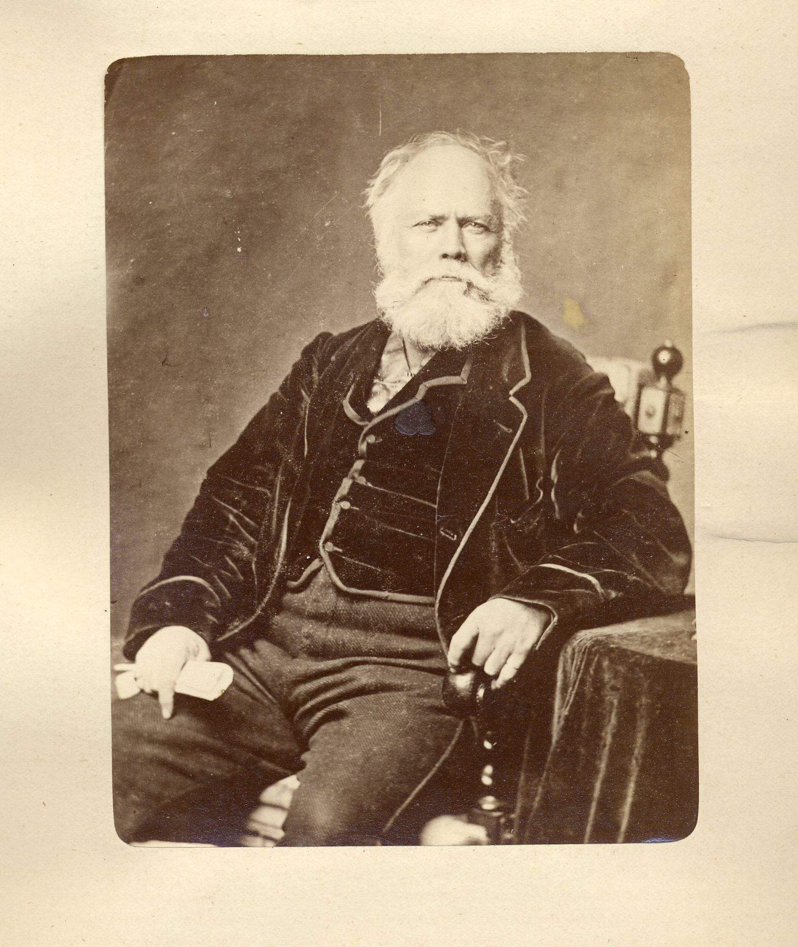 Sepia-tone photograph of a man aged about sixty, seated in a chair. His hair is white and he is slightly balding, with a thick, white, medium-length beard. He wears a dark velvet waistcoat and jacket, with trousers in a lighter material. His left arm rests on a table covered in a velvet tablecloth.