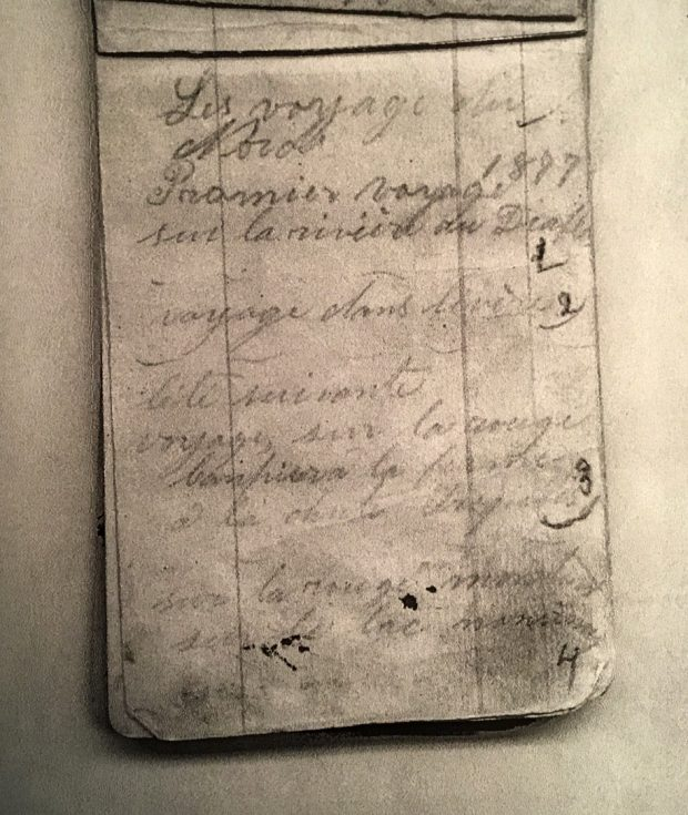 "Photograph of a page from a notebook. Handwritten in pencil are the words ""Les voyages du Nord. 1877, Premier voyage sur la rivière du Diable"" (""Travels Northward. 1877, first trip on the Diable River""). A number of other destinations follow."