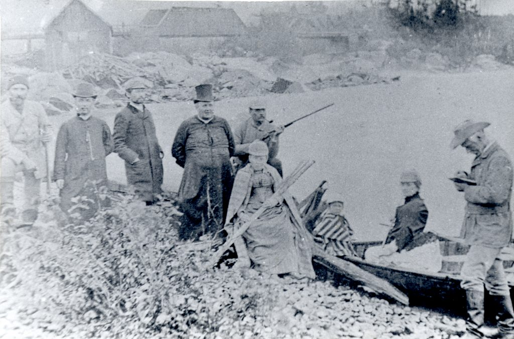 Black & white photograph of a group of people standing on a riverbank by a canoe: two priests, two women, a child, two men holding rifles, a man taking notes, and another man. Some wooden buildings and a wooden bridge are seen in the background.