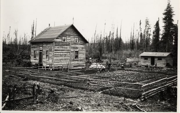 Black & white photograph of a pioneer home. It is a box-shaped house with wood siding and a simple pitched roof. Nearby is a small round-timber shed. To the right of the house is a large garden enclosed by a split-rail fence. Two adults work the garden.