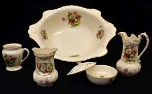 Colour photograph of a six-piece men's toilet service in porcelain. In front, left to right: receptacle for items, shaving scuttle, soap dish, and water jug. At the rear: shaving bowl. The porcelain objects are white, with flower motifs and gilt edges.