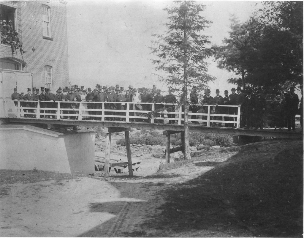 Black & white photograph of a group of people, mostly men, standing on a walkway in summer. The walkway leads to a large brick factory building. People are also seen perched higher up, in an opening on a higher floor of the factory. Many of those pictured are wearing top hats for the occasion.