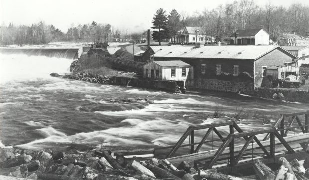 Black & white photograph of a landscape in spring. In the foreground at right, a small wooden bridge crosses a fast-flowing river with rapids; a pile of logs is also seen. Upstream, in the background at left, is a dam with water spilling over it forcefully. In the centre is an industrial brick building, and behind it, a house and a few farm buildings.