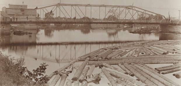 Sepia-tone photograph of an iron bridge and river in summer. People can be seen on the bridge deck and on the girders up above. A log boom is visible in the foreground, with some wooden buildings in the background.