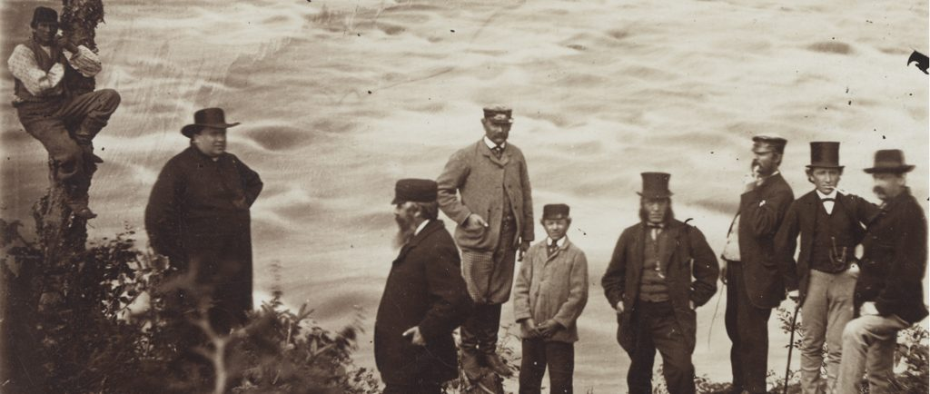 Black & white photograph of a group of nine people standing on the shore of a rushing river. At left, a man is perched partway up a tree trunk. Curé Labelle, a heavy-set man, is seen wearing a cassock and a wide-brimmed felt hat. At centre and right are six men and a teenaged boy wearing three-piece suits and top hats, caps or felt hats. Two of them are smoking pipes.