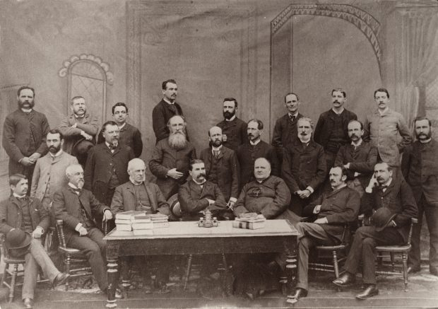 Black & white photograph depicting the 23 members of the Ministry of Agriculture and Colonization on September 1, 1889. Sixteen men stand behind group of a seven seated on chairs behind a table.