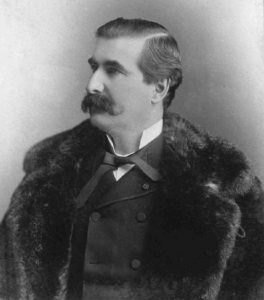 Black & white photograph of a man in his forties, with dark hair and a thick moustache. He wears elegant clothes beneath a fur coat.