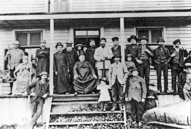 Black & white photograph of a group of around twenty people on the porch of a wooden house. In the centre of the group, Curé Labelle, a heavy-set man wearing a cassock, is seated in a chair. At right, on the ground in front of the porch, is a large birchbark canoe.