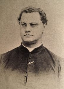 Sepia-tone photograph of a man in his thirties. He has close-cropped dark curly hair. He wears small oval eyeglasses. He wears a cassock, with a clerical collar.