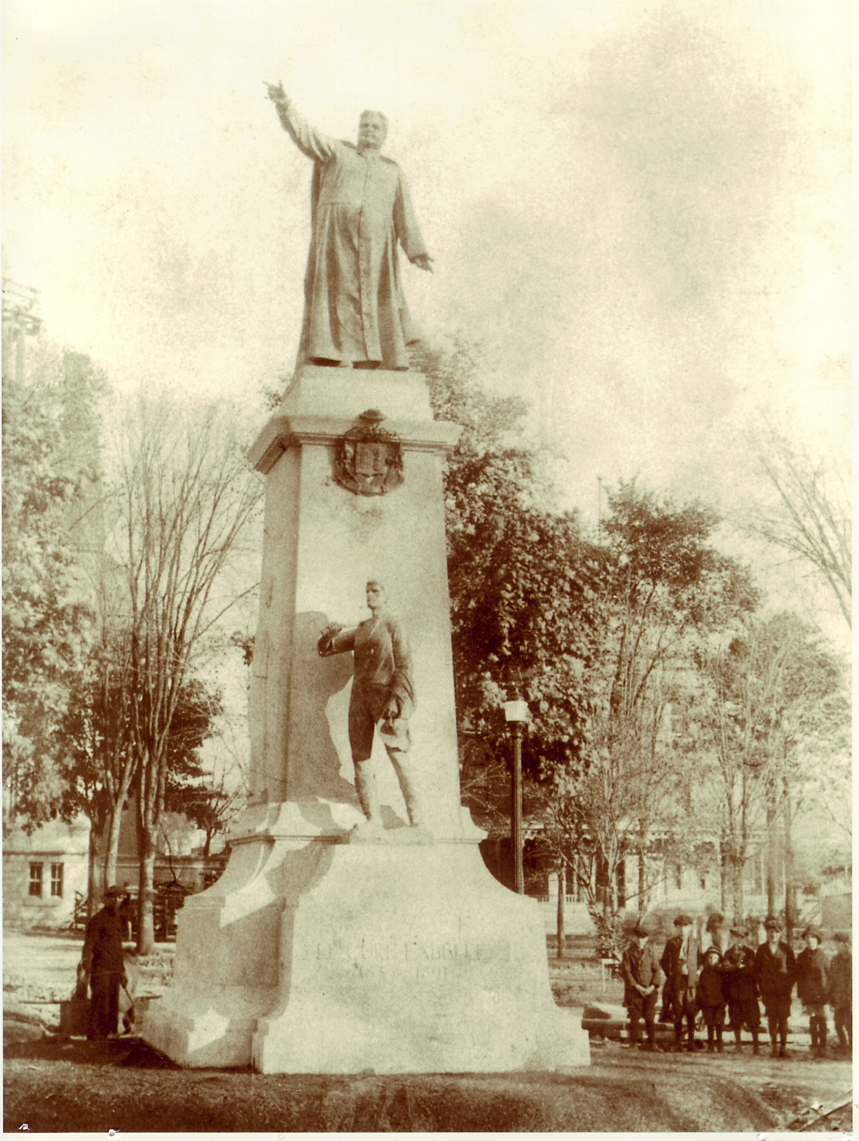 Black & white photograph of a statue of Curé Labelle pointing northward. The statue stands on an imposing pedestal. Below Labelle's feet is his coat of arms, and lower still, a smaller bronze statue of a pioneer. A man and his children are seen standing by the pedestal.