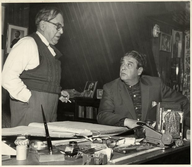 Black & white photograph of a man standing beside a desk, talking to other man seated behind it. The desk is covered with many items: a large, open book, a stapler, a pair of glasses, an inkwell and pen, and many other small objects.