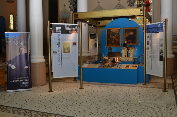 Colour photograph of exhibition panels with texts and images, surrounding display cases housing various objects.