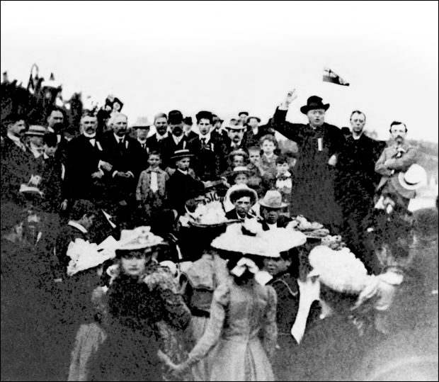 Black & white photograph of a crowd outdoors, surrounding an imposing figure, Curé Antoine Labelle. Several men are seen, along with a few women and children, all well dressed. Labelle wears a black cassock and black hat and is giving a speech; his mouth is open and his right arm is raised beside his head. His left art rests on his hip.