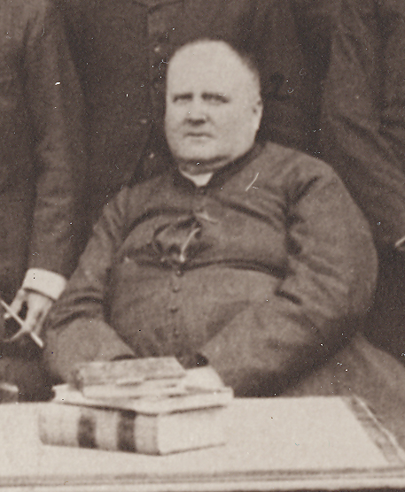 Black & white photograph of Curé Labelle. He is seated and, with his cassock unbuttoned and opened at the chest, his excess weight is conspicuous.