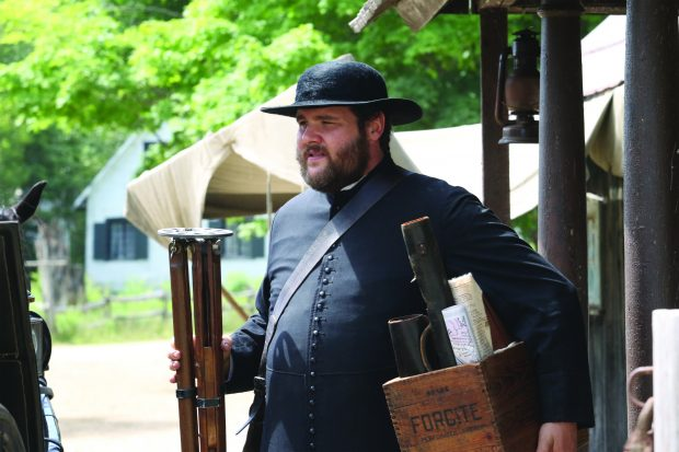Colour photograph of an actor playing the role of Curé Labelle. He wears a cassock and a hat, and carries a box of maps.