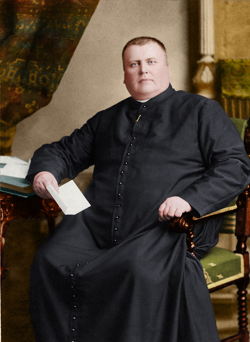 Colourized photograph of Curé Labelle seated at a desk, holding a letter. His right hand rests on the desk, and his left hand rests on the arm of his chair.