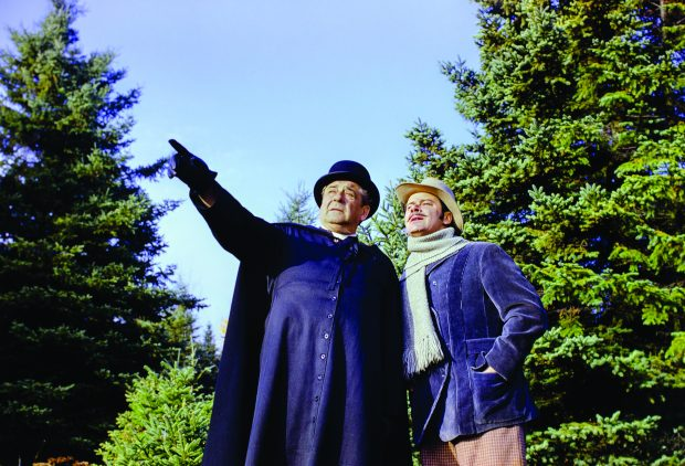 Colour photograph of two actors in a forest setting. A man in a cassock, playing Curé Labelle, points to something in the distance. The man accompanying him, wearing a coat, scarf and hat, stands close to him and gazes into the distance.