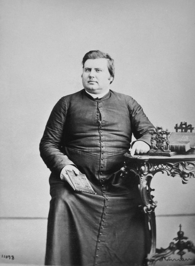 Black & white photographic portrait of a man aged thirty, fairly stout and with dark hair. He is seated, clad in a black cassock buttoned to the neck; his left arm rests on an ornately carved table and in his right hand he holds a book. His gaze is neutral and he is unsmiling.